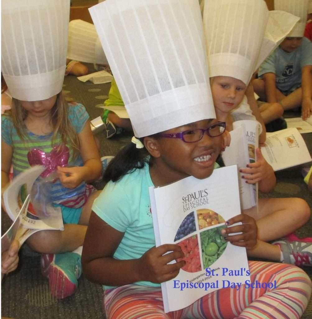students in chef hats with recipe books