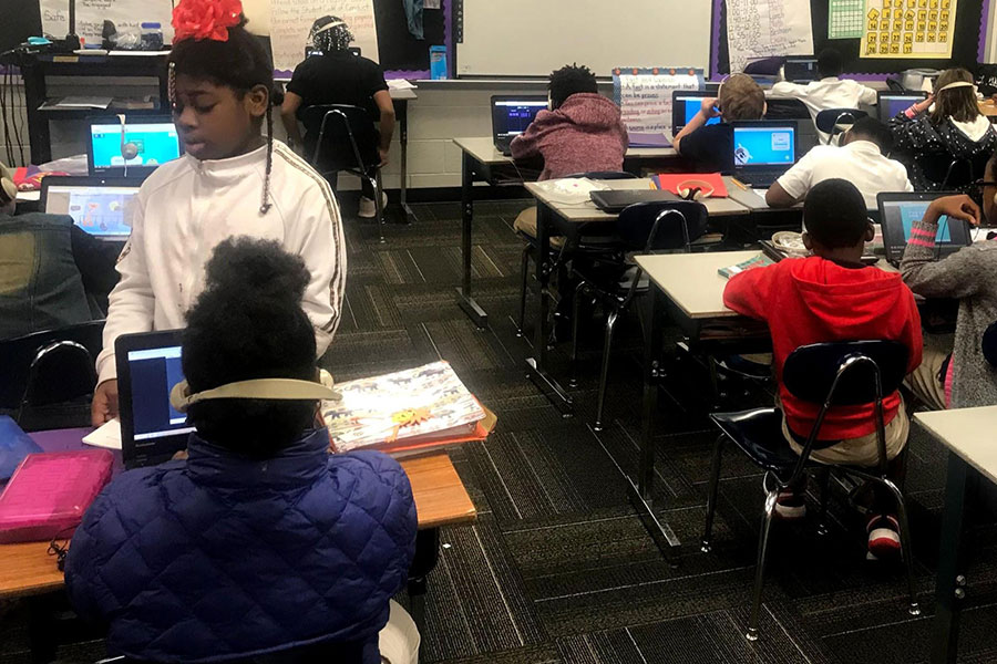 fifth graders completing math assignments