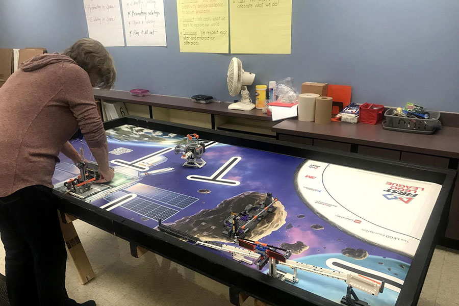 volunteers setting up table for robotics team