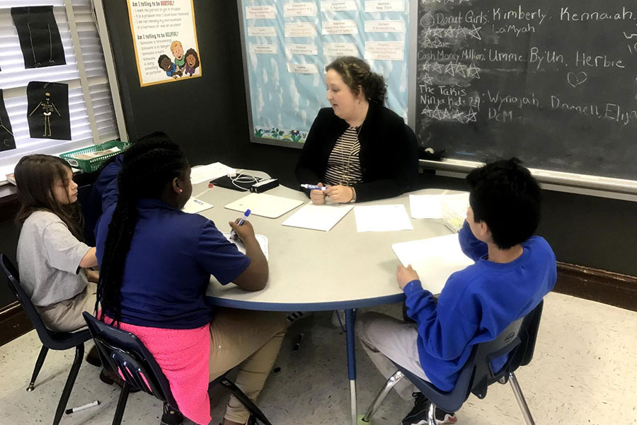 fourth graders working with teacher at table
