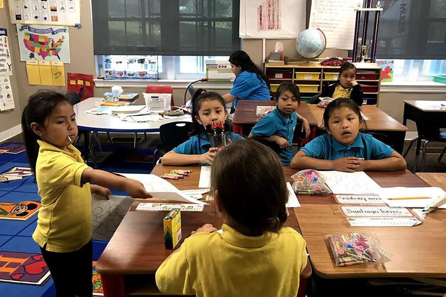 kindergarten students passing out papers