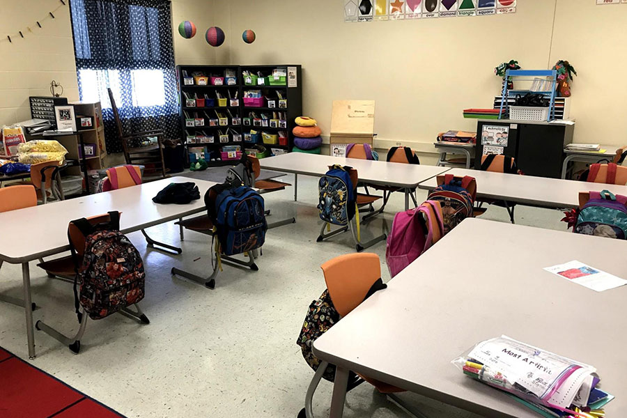 Student work areas with bookbags on chairs
