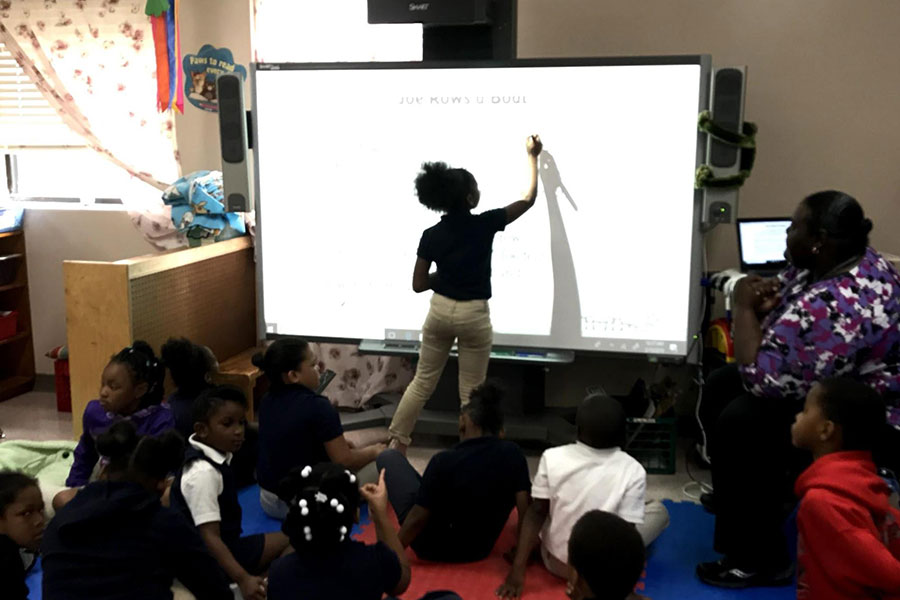 student using a smart board in classroom