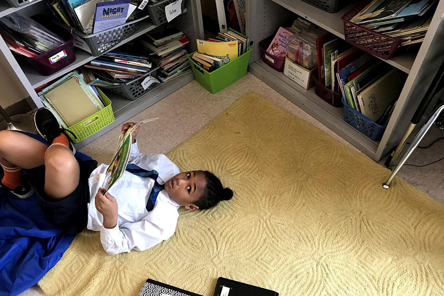 student reading in classroom corner library