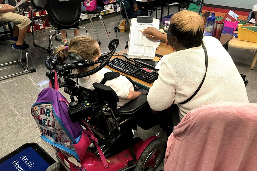 Third grade student in a wheelchair receiving help with her classwork.