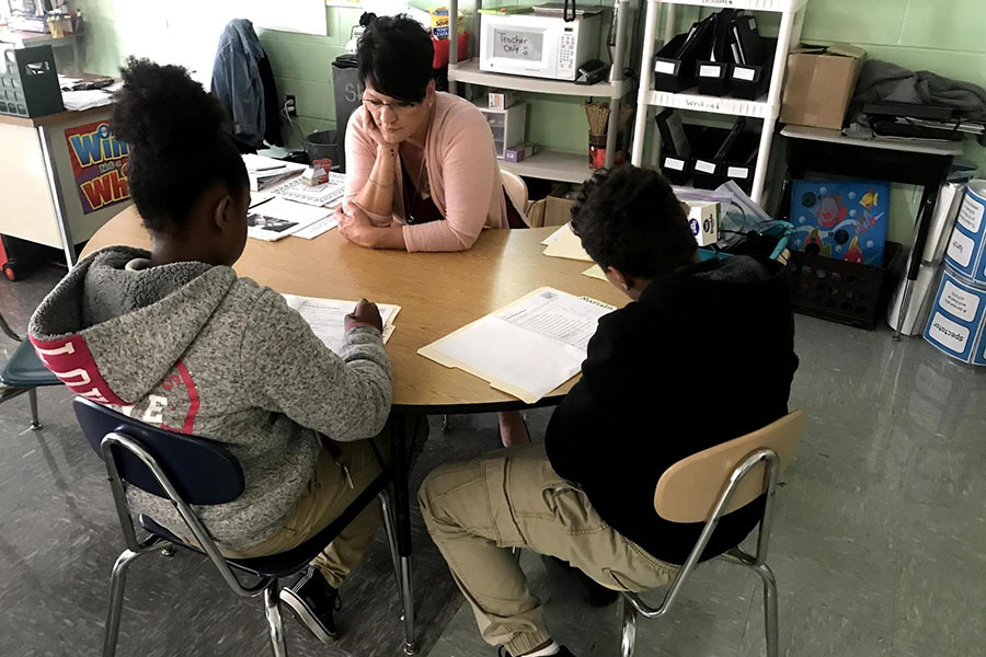 In sixth grade, these two students complete a reading assignment with their teacher