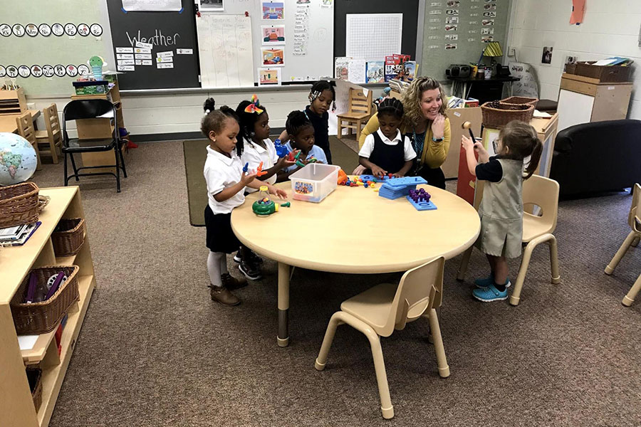 Pre-K students play games with their teacher.