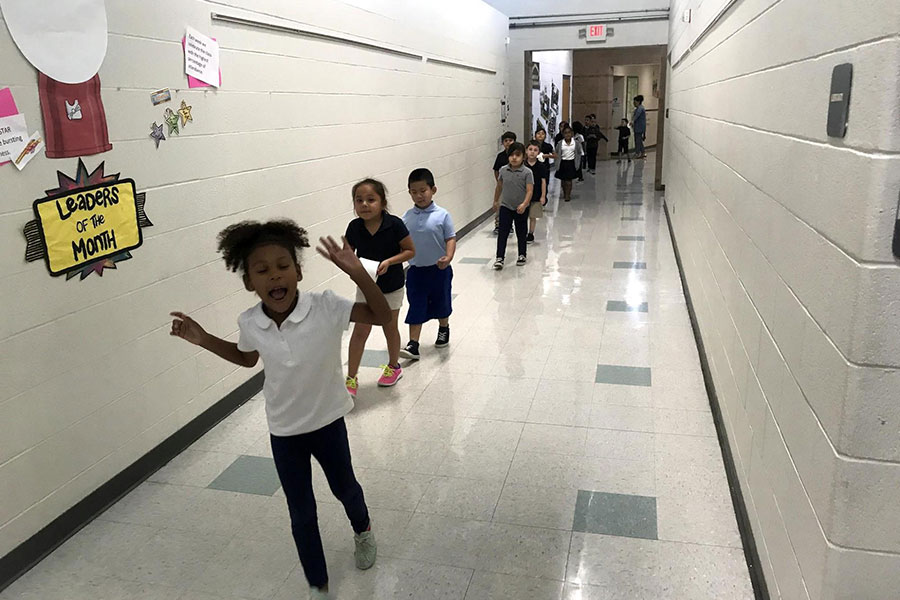 First grade students walking in a hallway.
