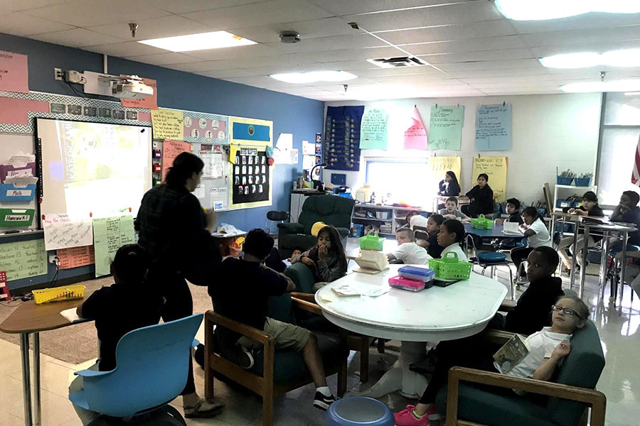 Third grade students reading with their teacher.