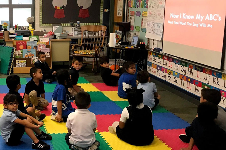 In this Kindergarten room, students complete a musical review their alphabet on the carpet