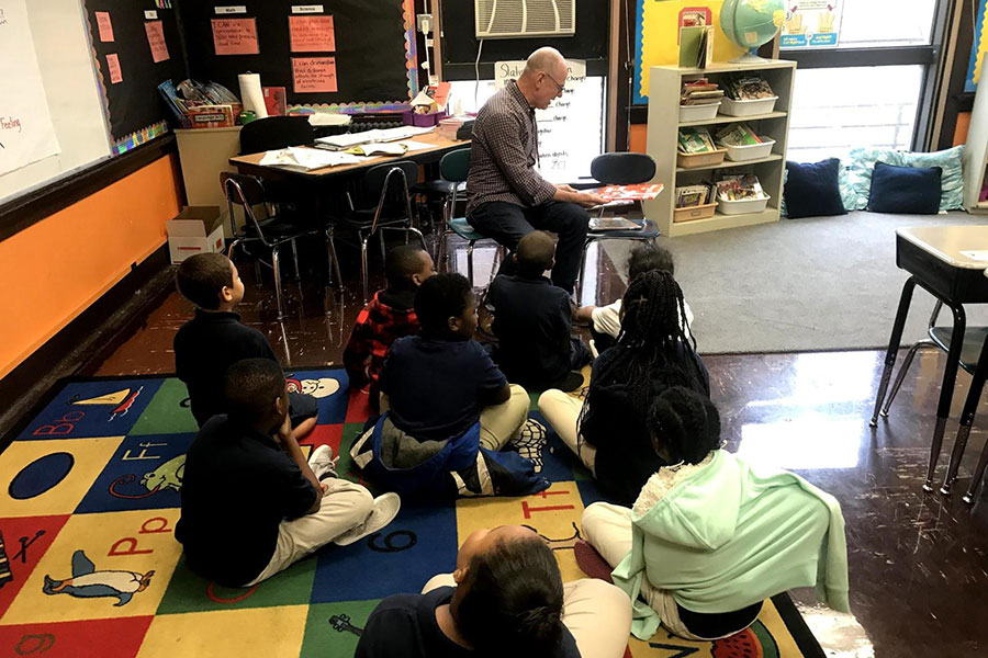Students listening to volunteer read story