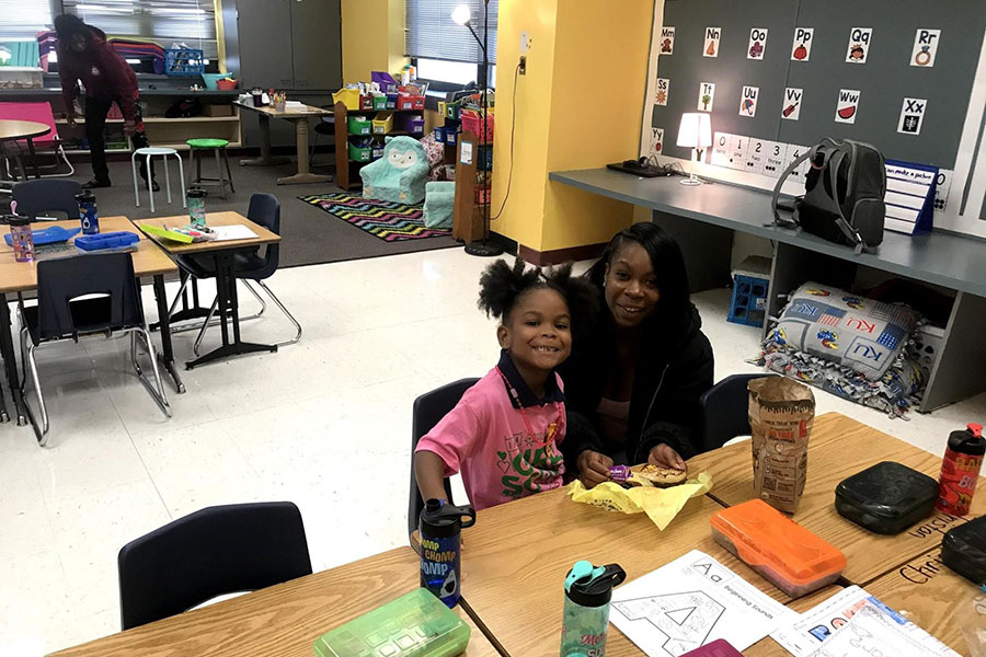 Student and parent having breakfast in classroom
