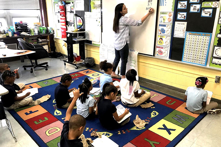 students working math problems with teacher